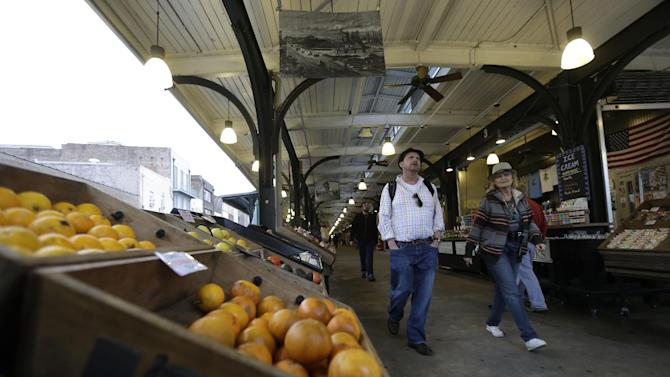 This Jan. 15, 2013 photo shows people walking through the French Market in New Orleans. The centuries-old commercial hub stretches for several city blocks along the bank of the Mississippi River in the French Quarter and includes Cafe du Monde, home of the deep-fried, sugar-coated beignet, a popular New Orleans pastry.  (AP Photo/Gerald Herbert)