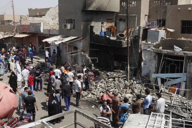 People inspect the scene of a bomb attack in Madain, about 15 miles (25 kilometers) southeast of Baghdad, Iraq, Monday, July 23, 2012. An onslaught of bombings and shootings killed scores of people ac
