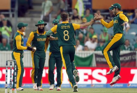 South Africa's Hashim Amla celebrates with team mates after catching Ireland's Ed Joyce out for a duck during their Cricket World Cup match at Manuka Oval in Canberra