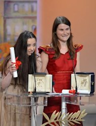Romanian actresses Cosmina Stratan (L) and Cristina Flutur speak on stage after being awarded with the Best Actress award during the closing ceremony of the 65th Cannes film festival in Cannes. The Two Romanians shared the Cannes best actress prize Sunday for their roles as best friends, a nun and the victim of a deadly &quot;exorcism&quot;, in Cristian Mungiu&#39;s &quot;Beyond the Hills&quot;