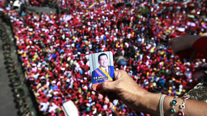 A supporter of Venezuela's late President Hugo Chavez holds a picture of him above a crowd waiting for Chavez's coffin to be taken from the hospital where he died on Tuesday, to a military academy where it will remain until his funeral in Caracas, Venezuela, Wednesday, March 6, 2013. Seven days of mourning were declared, all schools were suspended for the week and friendly heads of state were expected for an elaborate funeral Friday. (AP Photo/Ricardo Mazalan)
