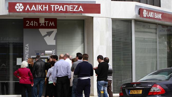 People queue to use the ATM of a closed branch of Laiki Bank in capital Nicosia, Thursday, March 21, 2013. The European Central Bank says it will keep emergency aid for Cyprus' troubled banks in place at least until Monday but will have to cut it off after that unless an international rescue program is drawn up. (AP Photo/Petros Karadjias)