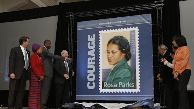 From left, Rep. Gary Peters, D-Mich., Deputy Postmaster Elaine Steele, Gen. Ronald Stroman, Sen. Carl Levin, D-Mich., Rep. John Conyers, D-Mich., Carolyn House Stewart, Alpha Kappa Alpha sorority International president, and Patricia Mooradian, president of The Henry Ford, help unveil the Rosa Parks' 100th birthday commemorative postage stamp at The Henry Ford in Dearborn, Mich., Monday, Feb. 4, 2013,  on what would have been the late civil rights icon's 100th birthday.  (AP Photo/Carlos Osorio)