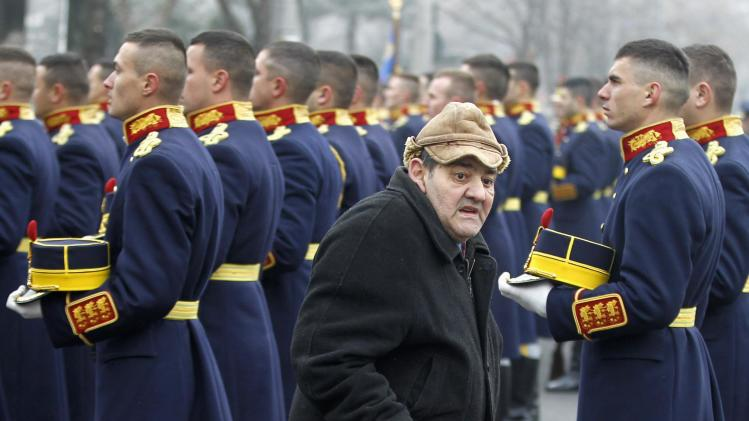 An elderly man walks past soldiers during ceremonies marking 24 years since 1989 bloody anti-communist Romanian revolution in Bucharest