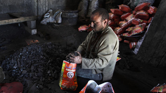 In this Sunday March 24, 2013 photo, a Palestinian worker fills bags with coal to be sold, in Jabalya refugee camp in the north of the Gaza Strip. In adapting to years of border blockades and shortages, Gazans have become experts at recycling and making new out of old including turning scrap wood into charcoal to be used for barbecue grills and water pipes in local restaurants and coffee houses. (AP Photo/Hatem Moussa)