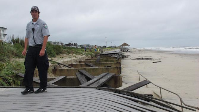In a Aug. 28, 2011 photo, Special Police Officer Kevin Preston inspects a damaged section of boardwalk in Spring Lake N.J., shortly after Tropical Storm Irene had passed by. Spring Lake had rebuilt its boardwalk from that storm shortly before Superstorm Sandy wrecked it again a year later. Now Spring Lake is among several Jersey shore towns considering a protective sea wall to be built east of its boardwalk as a protective measure for the walkway. (AP Photo/Wayne Parry)