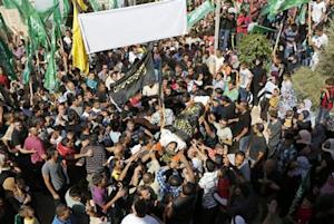 Palestinians hold Hamas and Islamic Jihad flags during the funeral of Mohammed Assi in the West Bank village of Beit Liqiya near Ramallah