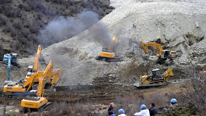 In this photo released by China's Xinhua News Agency, earthmovers remove rocks and mud on the scene where a landslide hit a mining area in Maizhokunggar County of Lhasa, southwest China's Tibet Autonomous Region, on Friday, March 29, 2013.  The large landslide trapped dozens of workers in the gold mining area, state media reported. (AP Photo/Xinhua, Chogo) NO SALES