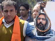 A Hindu activist holds up a burning poster of Mohammed Afzal Guru after his execution in New Delhi on February 9, 2013. Guru -- a Kashmiri separatist -- was executed in New Delhi over his role in a deadly attack on the Indian parliament in 2001 -- triggering protests on both sides of the border in disputed Kashmir