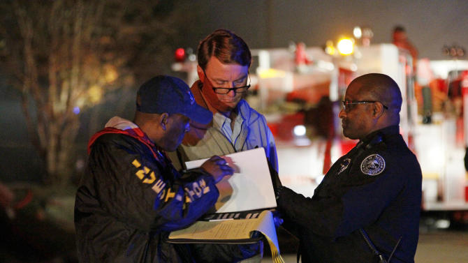 Investigators review notes as fire fighters combat a fire in a west Jackson, Miss., home where authorities say a small plane carrying three people crashed shortly after 5 p.m. Tuesday evening, Nov. 13, 2012. The home's resident is believed to have escaped but authorities have not released names of plane's passengers.  (AP Photo/Rogelio V. Solis)