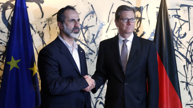 German Foreign Minister Guido Westerwelle, right, and Sheikh Moaz Al-Khatib, President of the National Coalition of Syrian Revolutionary and Opposition Forces, shake hands during the Security Conference in Munich, southern Germany, on Friday, Feb. 1, 2013. The 49th Munich Security Conference starts Friday afternoon with experts from 90 delegations including US Vice President Joe Biden. (AP Photo/Matthias Schrader)