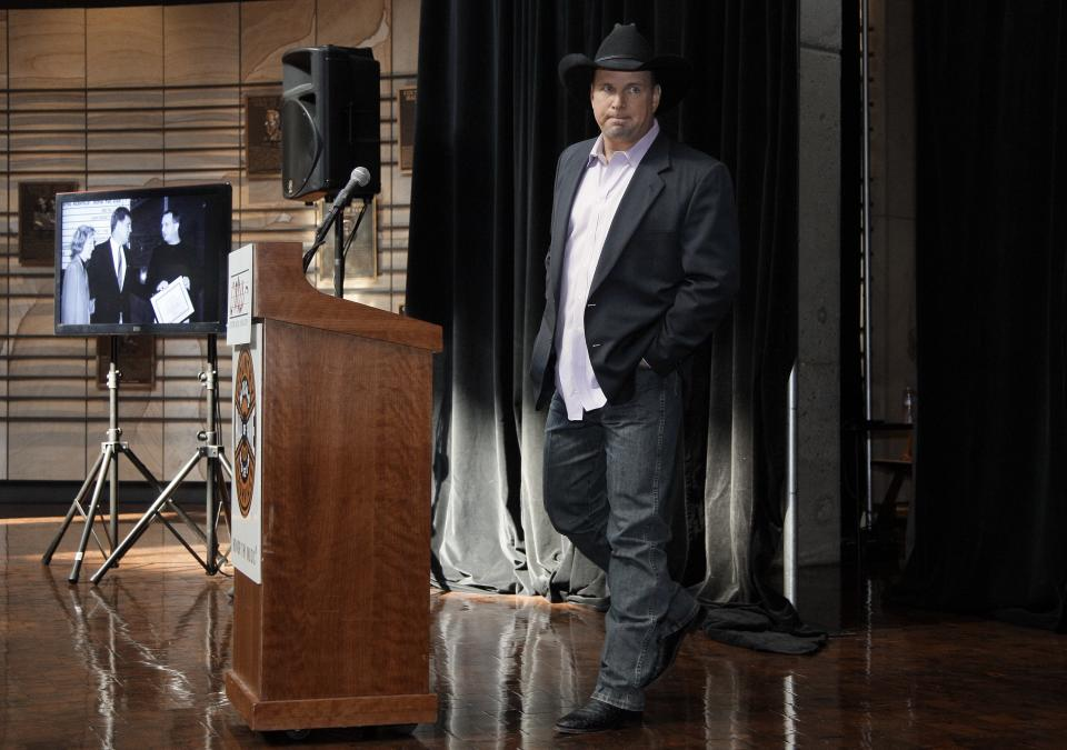 "Garth Brooks walks to the podium Tuesday, March 6, 2012, during the announcement that he will be inducted into the Country Music Hall of Fame in Nashville, Tenn. Brooks, Connie Smith, and Hargus ""Pig"" Robbins will become the newest members. The announcement was held in the Hall of Fame. (AP Photo/Mark Humphrey)"
