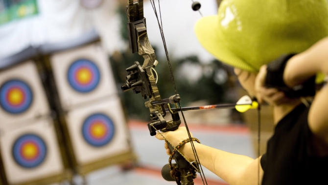 """In this April 13, 2012 photo, a young archer  participates in the youth archery league at Targeteers Archery in Saddle Brook, N.J. In schools and backyards, for their birthdays and out with their dads, kids are gaga for archery a month after the release of """"The Hunger Games."""" Archery ranges around the country have enjoyed a steady uptick among kids of both sexes in the movie's lead-up, though 16-year-old heroine Katniss Everdeen, the archery ace seems to resonate with girls more than boys. (AP Photo/Charles Sykes)"""