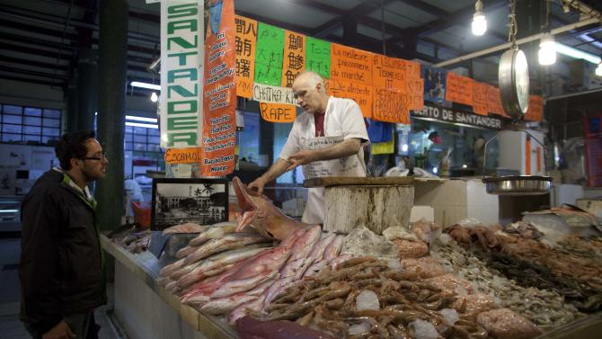 In this July 27, 2012 photo, U.S. Chef Christopher Kostow, left, talks to a vendor as he shops at Mercado San Juan Pugibet, the most gourmet market in Mexico City. (AP Photo/Alexandre Meneghini)