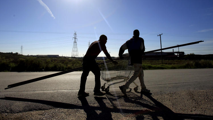 In this picture dated Nov. 3, 2012, African immigrants push a shopping cart loaded with scrap metal, near the village of Nea Philadelphia, in northern Greece. When Greece adopted the euro, it poured billions into modernizing its infrastructure, building spectacular bridges, highways, and a brand new rail transit network for Athens. Now, locked in recession and crushed by debt, Greeks are targeting many of those projects, gouging out the metal and selling it for scrap to feed ravenous demand driven by China and India. (AP Photo/Nikolas Giakoumidis)