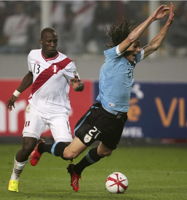 Peru's Advincula tackles Uruguay's Cavani during their 2014 World Cup qualifying soccer match in Lima