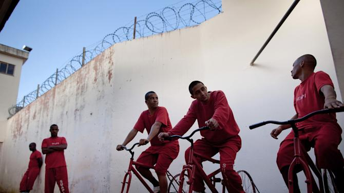 In this Friday, July 6, 2012, inmates pedal stationary bikes to charge car batteries at a prison in Santa Rita do Sapucai, Brazil. An innovative program allows inmates at this medium-security prison to shave days off their sentence in exchange for riding stationary bikes hooked up to converted car batteries that are used to illuminate Santa Rita do Sapucai's town square. (AP Photo/Felipe Dana)