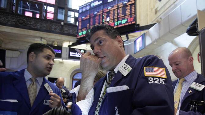FILE - In a July 31, 2012 file photo trader William McInerney, center, works on the floor of the New York Stock Exchange.  U.S. stocks fell Monday, Aug. 13, 2012 as evidence piled up that the global economic slowdown is dragging on Asia.  (AP Photo/Richard Drew, file)