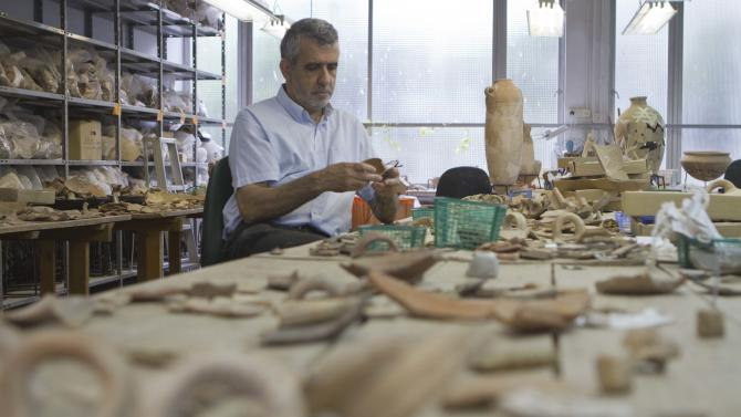 In this photo taken Wednesday, May 23, 2012 professor Israel Finkelstein sits in his desk at the Tel Aviv University, Israel. Israeli archaeologists have unearthed a stash of rare ancient jewelry near the site of the biblical Armageddon in the north of the country. Finkelstein, who co-directed the dig, said this week that the find offers a rare glimpse into ancient Canaanite high society. The 3,000-year-old jewelry was found inside a ceramic vessel, suggesting the owner hid them before fleeing, he said. (AP Photo/Dan Balilty)