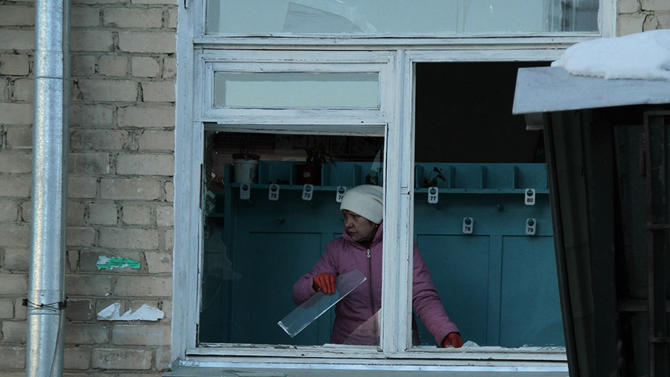 In this photo provided by Chelyabinsk.ru a woman cleans away glass debris from a window after a meteorite explosion over Chelyabinsk region on Friday, Feb. 15, 2013. A meteor exploded in the sky above Russia on Friday, causing a shockwave that blew out windows injuring hundreds of people and sending fragments falling to the ground in the Ural Mountains.  The Russian Academy of Sciences said in a statement hours after the Friday morning fall that the meteor entered the Earth's atmosphere at a speed of at least 54,000 kph (33,000 mph) and shattered about 30-50 kilometers (18-32 miles) above ground. The fall caused explosions that broke glass over a wide area. (AP Photo/ Yevgenia Yemelyanova, Chelyabinsk.ru)