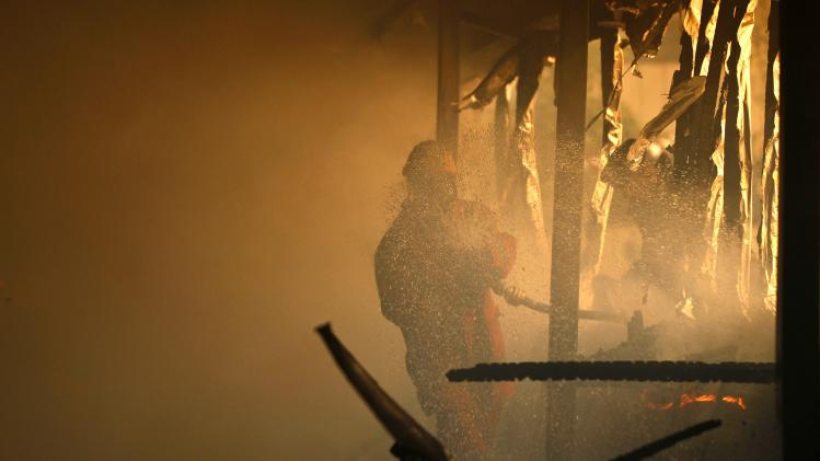 A fire fighter attempts to extinguish a fire at a nightclub undergoing renovations in Kenya's capital Nairobi