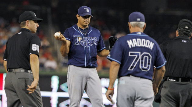 Tampa Bay Rays manager Joe Maddon (70) heads to the mound to talk with relief pitcher Joel Peralta and the umpires during the eighth inning of the Rays' baseball game against the Washington Nationals at Nationals Park on Tuesday, June 19, 2012, in Washington. Peralta was ejected without throwing a pitch after the umpires found a foreign substance on his glove. (AP Photo/Alex Brandon)