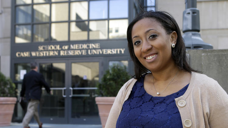 In this photo taken April 23, 2013, Lauren Howie, 27, poses outside the School of Medicine at Case Western Reserve University in Cleveland. America's blacks voted at a higher rate than other minority groups in 2012 and by most measures surpassed the white turnout for the first time. In Ohio, a battleground state where the share of eligible black voters is more than triple that of other minorities, Howie didn't start out thrilled with President Barack Obama in 2012. She felt he didn't deliver on promises to help students reduce college debt, promote women's rights and address climate change, she said. But she became determined to support Obama as she compared him with Romney.  (AP Photo/Mark Duncan)