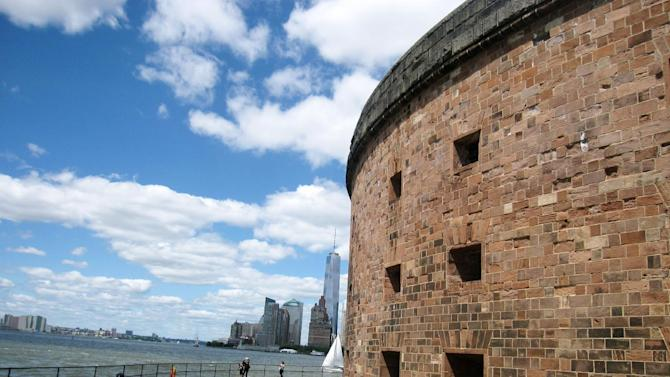 This June 6, 2014 photo shows Castle Williams, a 19th century fort located on Governors Island in New York City, with a view of 1 World Trade Center and Lower Manhattan in the distance. Castle Williams was used as barracks and a prison on the island, which is a former military and Coast Guard facility. Now a national park site, the island is open daily to visitors through the summer. It's dotted with green lawns, outdoor art and historic buildings and it offers a variety of events and activities, along with scenic views of Manhattan. (AP Photo/Beth J. Harpaz)