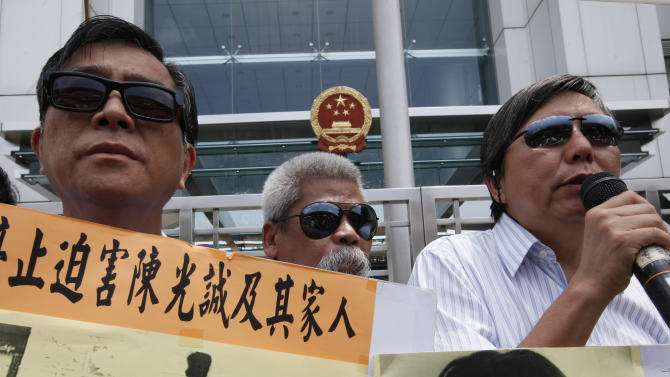 Pro-democracy protesters wearing sunglasses, hold placards with picture of  blind Chinese legal activist Chen Guangcheng, third left, with his family and Chinese activist He Peirong, right,  outside the China's Liaison Office in Hong Kong Monday, April 30, 2012 as they urge Beijing government stop persecution of Chen. A U.S. rights campaigner says a deal securing U.S. asylum for the blind Chinese legal activist who fled house arrest is expected in the coming 24 to 48 hours.  (AP Photo/Kin Cheung)