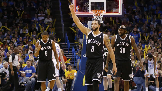 Brooklyn Nets guard Alan Anderson (6), guard Deron Williams (8) and forward Reggie Evans (30) celebrate as they walk off the court at the end of the third quarter of an NBA basketball game against the Oklahoma City Thunder in Oklahoma City, Thursday, Jan. 2, 2014. Oklahoma City won 95-93. (AP Photo/Sue Ogrocki)
