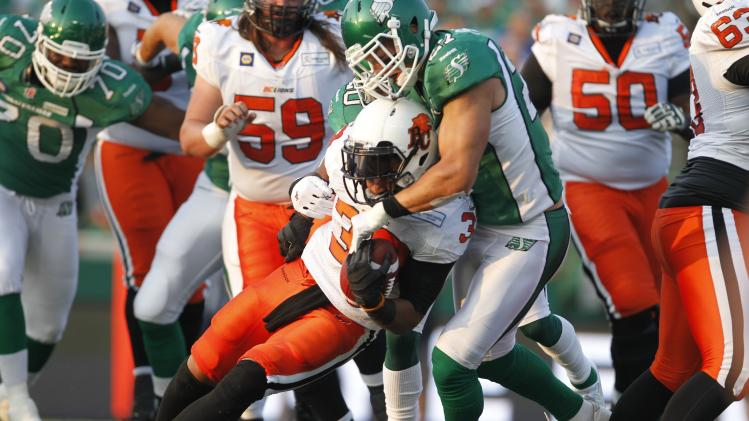 Lions running back Harris gets taken down by Roughriders linebacker Peters during the first half of their CFL football game in Regina