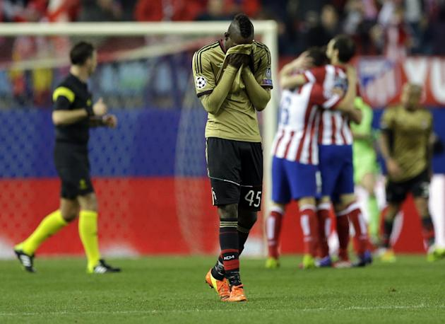 AC Milan's Mario Balotelli walks on the pitch as Atletico Madrid players celebrate in background, during a Champions League, round of 16, second leg, soccer match between Atletico Madrid and AC Mi