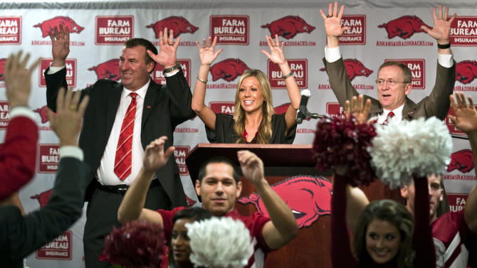 """Arkansas football coach Bret Bielema, top left, his wife, Jen, center, and athletic director Jeff Long, right, """"call the hogs"""" during a news conference to announce Bielema's hire in Fayetteville, Ark., Wednesday, Dec 5, 2012. Bielema, who will be paid $3.2 million annually for six years, replaces interim coach John L. Smith, who was hired after Bobby Petrino was fired in April. (AP Photo/April L. Brown)"""