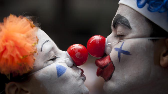 """A couple dressed as clowns participate in the """"Cordao da Bola Preta"""" street carnival parade in Rio de Janeiro, Brazil, Saturday, Feb. 9, 2013. According to Rio's tourism office, Rio's street Carnival this year will consist of 492 block parties, attended by an estimated five million Carnival enthusiasts. (AP Photo/Felipe Dana)"""