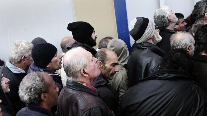 People wait to enter an indoor gym hall for a Christmas meal for the homeless and the poor in Athens