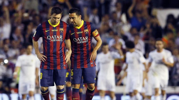 Barcelona's Xavi and Messi talks after losing to Real Madrid at the end their King's Cup final soccer match at Mestalla stadium in Valencia