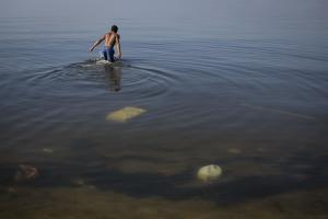 In this May 15, 2014 photo, a man jumps into the polluted …
