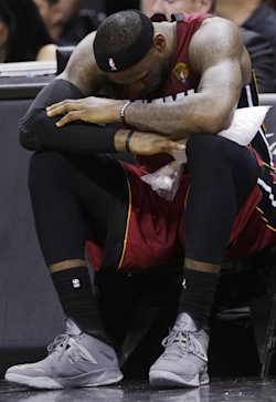 LeBron James sits on the bench with ice on his leg. (AP)