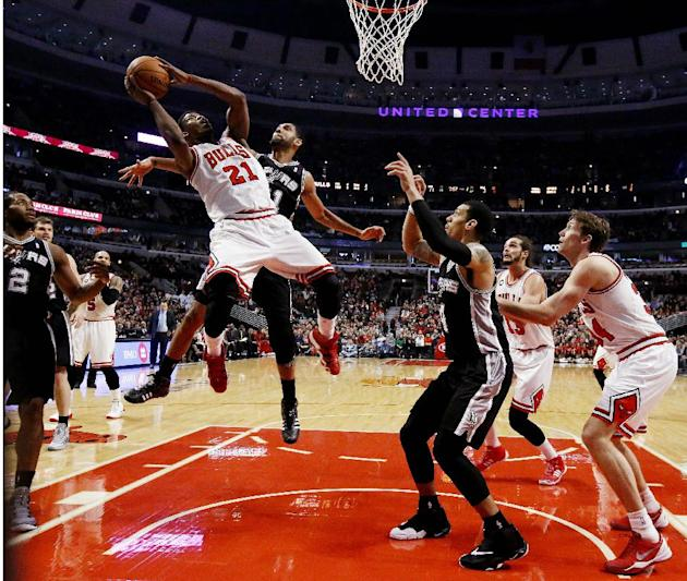 Chicago Bulls shooting guard Jimmy Butler (21) shoots over San Antonio Spurs power forward Tim Duncan, rear, during the first half of an NBA basketball game on Tuesday, March 11, 2014, in Chicago