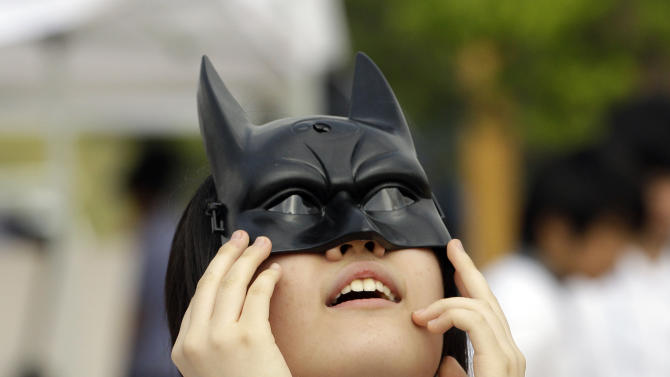 South Korean woman wears a mask of hero character with special glasses on, observes the transit of venus at National Science Museum in Gwacheon, south of Seoul, South Korea, Wednesday, June 6, 2012. From the U.S. to South Korea, people turned their attention to the daytime sky on Tuesday and early Wednesday in Asia to make sure they caught the rare sight of the transit of Venus. The next one won't be for another 105 years. (AP Photo/Lee Jin-man)
