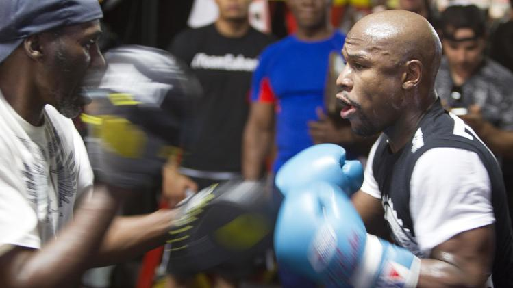 WBC/WBA welterweight champion Floyd Mayweather Jr. of U.S. works on timing his uncle and trainer Roger Mayweather during a media day at the Mayweather Boxing Club in Las Vegas