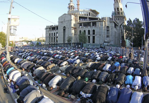 Thousand of Russian Muslims perform Eid al-Fitr prayers that mark the end of the holy fasting month of Ramadan outside the main Mosque in Moscow, Russia, Sunday, Aug.