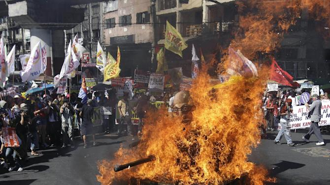 Protesters watch an effigy of Philippine President Benigno Aquino III on board a mock tank set on fire by them as they commemorate International Human Rights Day near the Presidential Palace in Manila, Philippines, on Monday, Dec. 10, 2012. The group called the Aquino administration alleged human rights violators. (AP Photo/Aaron Favila)