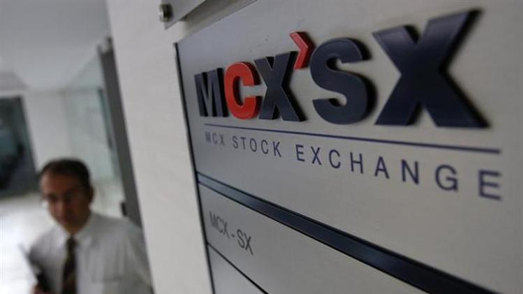 A staff member walks past the MCX-SX logo at their Exchange Square building in Mumbai February 11, 2013.