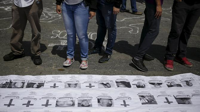 People stand in front of a banner with names and photographs of victims of violence during the protests against Nicolas Maduro's government in 2014, in Caracas