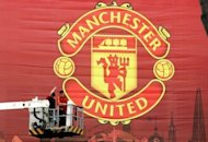 Manchester United shares opened barely higher than their $14 cut-price initial public offering Friday, adding a bare five cents as the overall market slumped