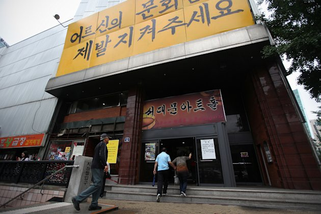 "Patrons of Seoul's last old-style one-screen cinema arrive for the theater's last screening at Seodaemun Art Hall in Seoul, South Korea, Wednesday, July 11,2012. Seoul's last old-style one-screen cinema, soon to be knocked down and replaced by a new tourist hotel, played its final movie Wednesday - the Italian classic ""The Bicycle Thief."" The letters on a banner at top read "" ""Please secure culture of elders"". (AP Photo/Hye Soo Nah)"