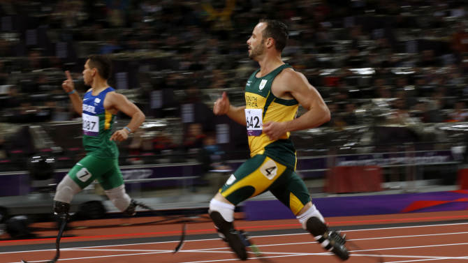 Brazil's Alan Fonteles Cardoso Oliveira, left, celebrates after running in to win the gold medal ahead of South Africa's Oscar Pistorius, right, who took the silver medal in the men's 200m T44 category final during the athletics competition at the 2012 Paralympics, Sunday, Sept. 2, 2012, in London.  (AP Photo/Matt Dunham)