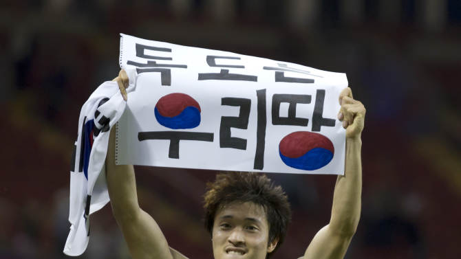 "FILE - This is a  Friday, Aug. 10, 2012 file photo of South Korea's Park Jong-woo as he holds up a banner reading ""Dokdo is our Territory,"" referring to the largely uninhabited islets, midway between South Korea and Japan, after his team won their bronze medal men's soccer match against Japan, at the 2012 London Summer Olympics, at the Millennium Stadium in Cardiff, Wales.  An official  Tuesday Feb. 12, 2013, familiar with the decision says South Korea's Park Jong-woo who displayed a political banner after a match at the London Olympics will receive his bronze medal. (AP Photo/Jon Super, File)"