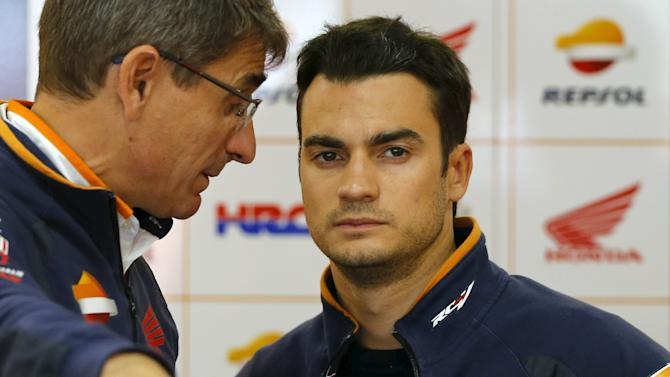 Honda MotoGP rider Dani Pedrosa of Spain talks with a team member in his garage during qualifying session for Sunday's Japanese Grand Prix at the Twin Ring Motegi circuit